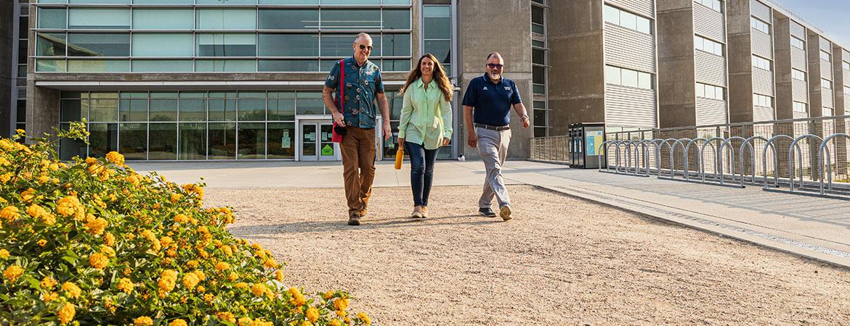 Trevor Hirst, Linda Hirst and Arturo Durazo taking a walk past Biomedical Sciences & Physics building, home of HSRI