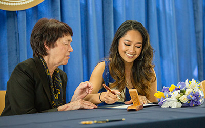 Chancellor Leland and Monique de Villa sign the Marinelo Sadsad and Amercia de Villa Endowed Scholarship.