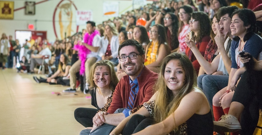 Students and teachers are seated on the floor and bleachers in a high school gymnasium while attending a pep rally in Merced.