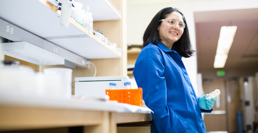 Professor Clarissa Nobile wearing a blue lab coat, teal-colored gloves, and safety goggles leans against a bench in her laboratory.